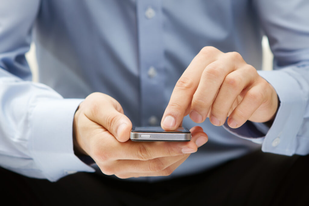 man holding an iphone with finger on the screen