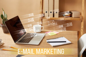 email makreintg desk with laptom computer and envelopes flying away